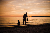 father and son on a beach at sunset
