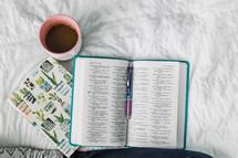 mug, Bible, and journal on a bed