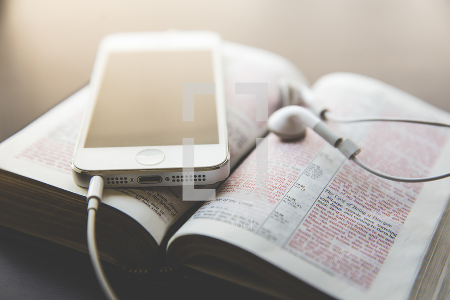 iPhone and earbuds on a Bible