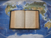an open Bible on a world map