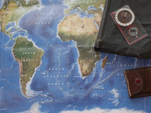 Bible, journal, compass, on a world map
