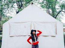 Woman in a hat standing before a white canvas tent.