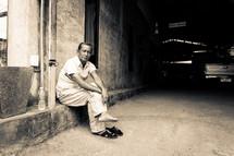 a man sitting on a curb resting his feet