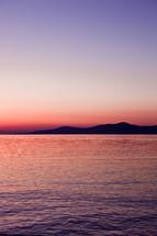 pink sky over a coastal mountain
