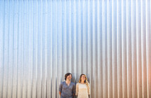 Couple standing in front of metal wall