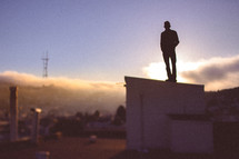 A silhouetted man stands a top a building a dawn