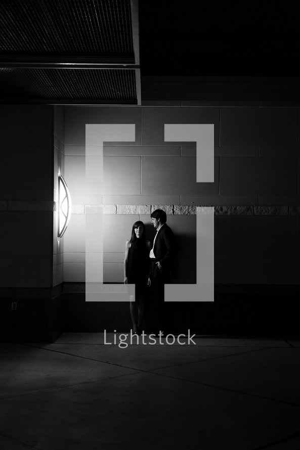 man and woman standing in front of a concrete wall at night