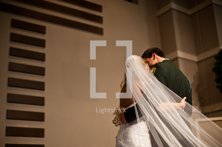 bride and military groom kissing