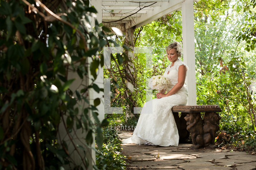 Bride sitting on a bench with flowers