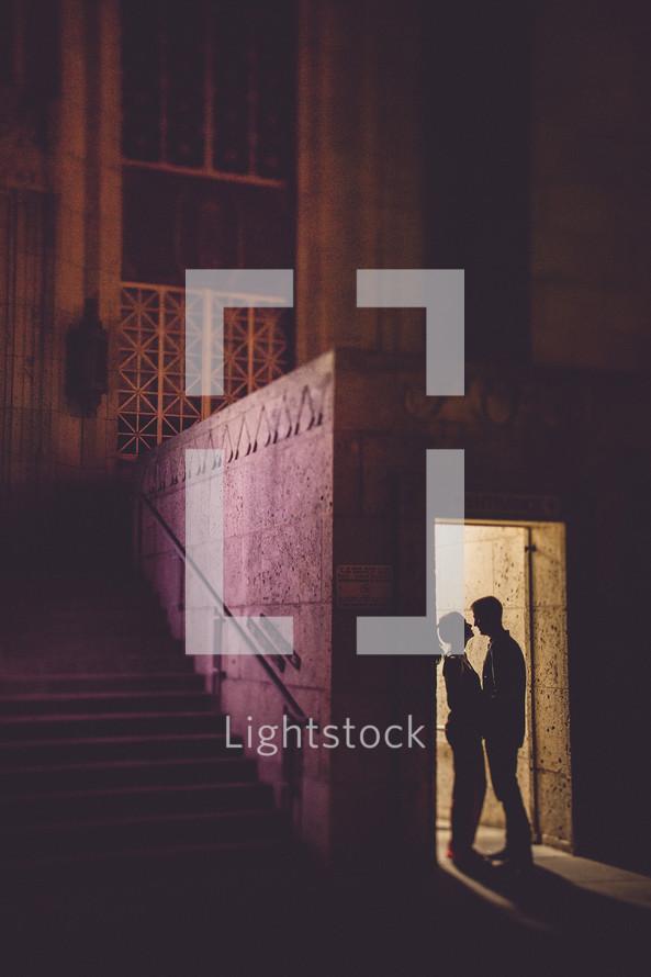 Couple standing in doorway holding hands