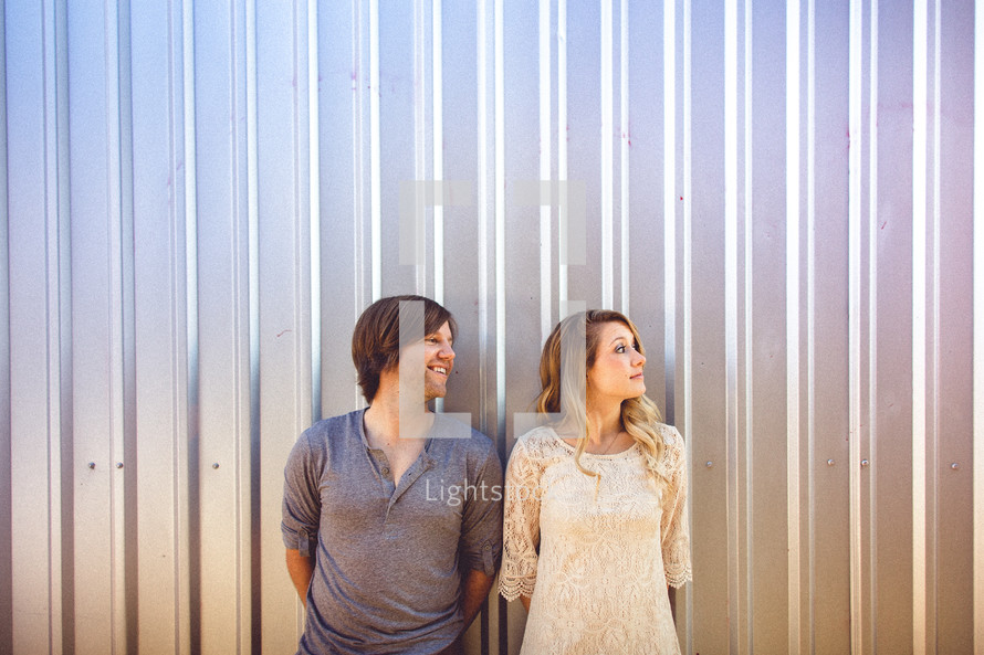 man and woman standing in front of a tin building