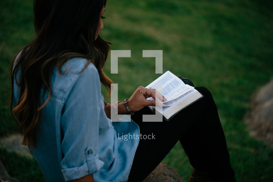 a woman sitting on a rock reading a Bible outdoors