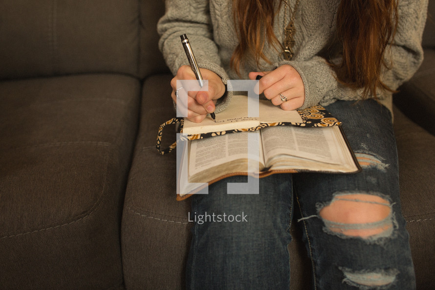 teen girl reading a Bible at a Bible study