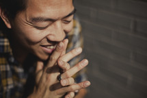 A man praying with fingers laced