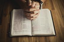 A man praying while reading his Bible