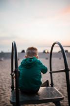 a child on a slide on a beach