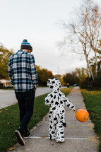 child trick-or-treating with dad
