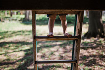 child's feet on a ladder