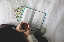 a woman reading a Bible sitting on her bed drinking coffee