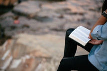 A young woman sits outside on a rock and reads the Bible.