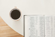 tea cup and an open Bible