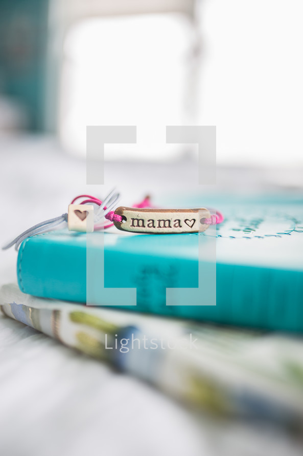 mama bracelet on a stacks of books