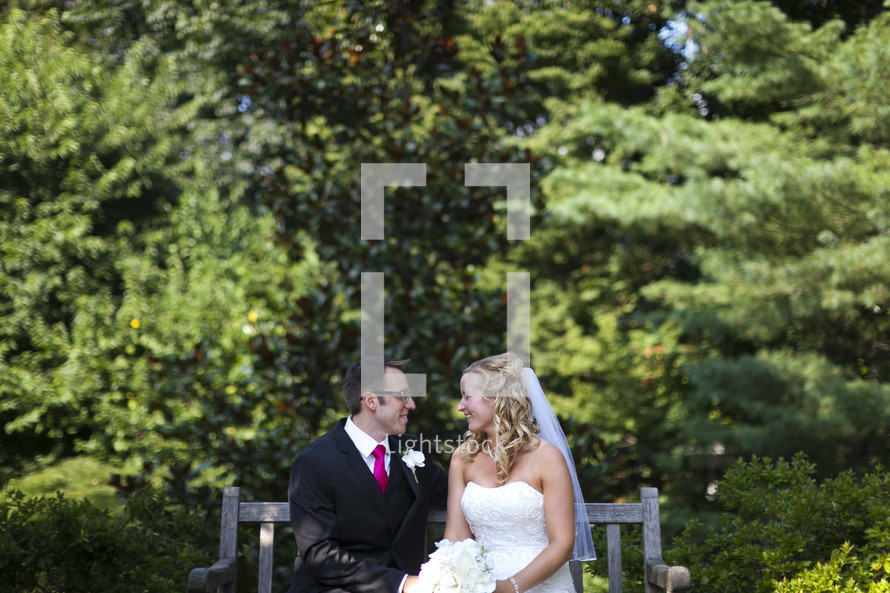 Happy bride and groom sitting on bench