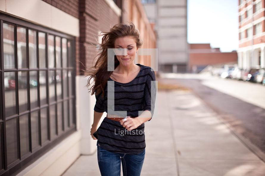 Woman walking down sidewalk