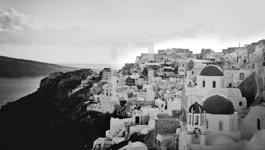Islamic homes on mountainside with ocean in the background.