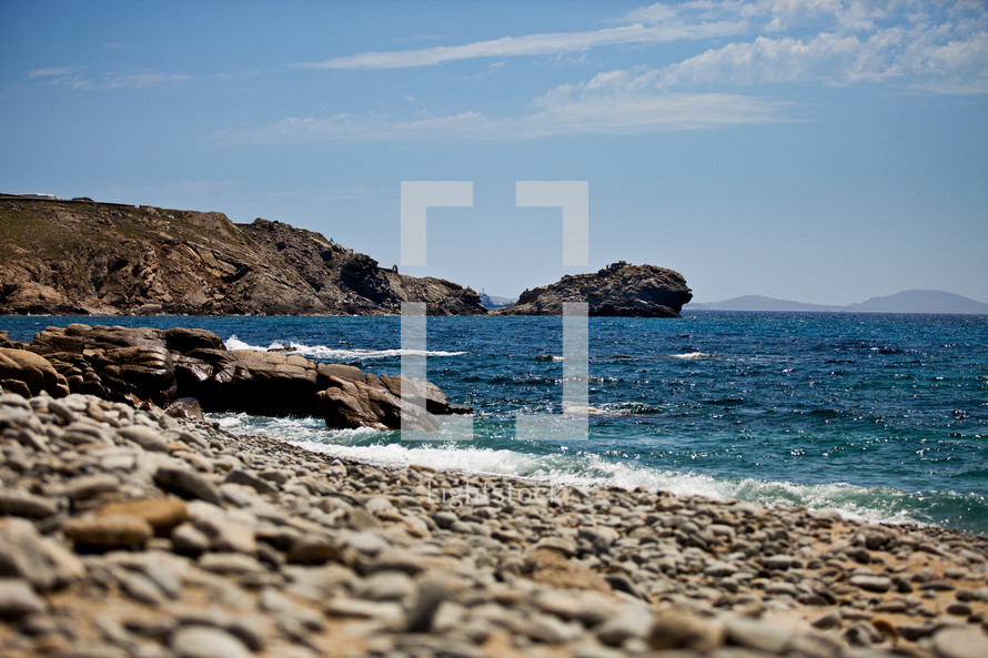 Rocky shore with blue ocean and mountains on the horizon.