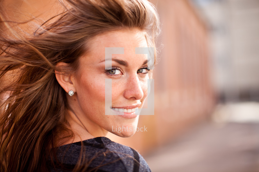 smiling woman with her hair blowing