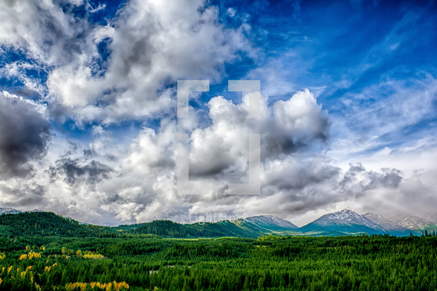 A soft and diverse cloud formation hovers over the forest-covered Cascade mountain range, allowing the fall-touched trees to cast their golden tones and the rich, green firs to still make their statement.