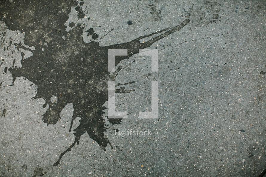 Tar splattered on concrete