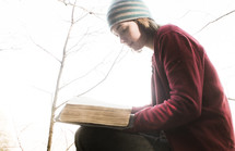 a woman reading a Bible outdoors in fall