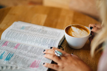 A woman reads a Bible and holds a cup of latte'.