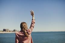 Woman raising arm gazing at ocean
