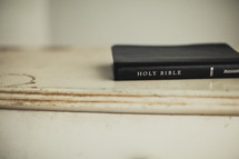 A Bible rests on a piece of white wood