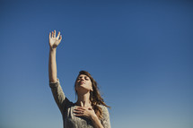 woman with hand raised and hand over her heart