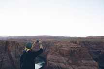 man taking a picture of a canyon with his cellphone