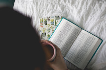 a woman reading a Bible with coffee
