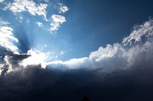 Clouds move in to overtake the sun and cast rays of light from what looks like a glowing cloud formation. Darkness looms where the sun cannot penetrate.