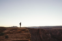 man standing at the edge of a mountain