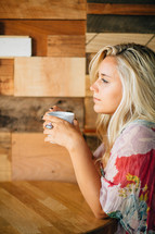 A thoughtful young woman holds a cup of coffee.