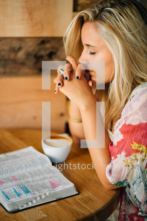 teen girl praying and an open Bible