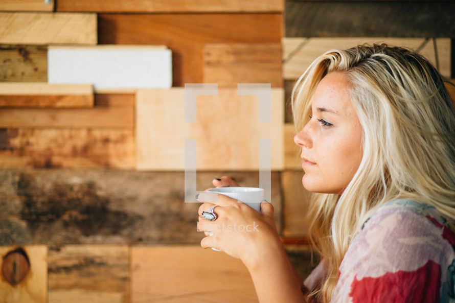A thoughtful young woman holds a coffee cup.