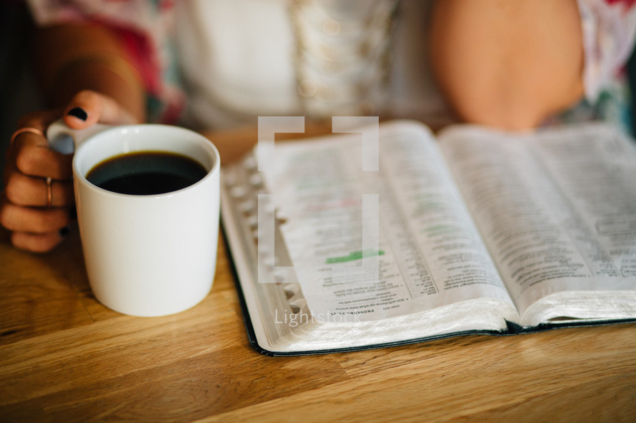 A young woman sits with a cup of coffee and an open Bible.