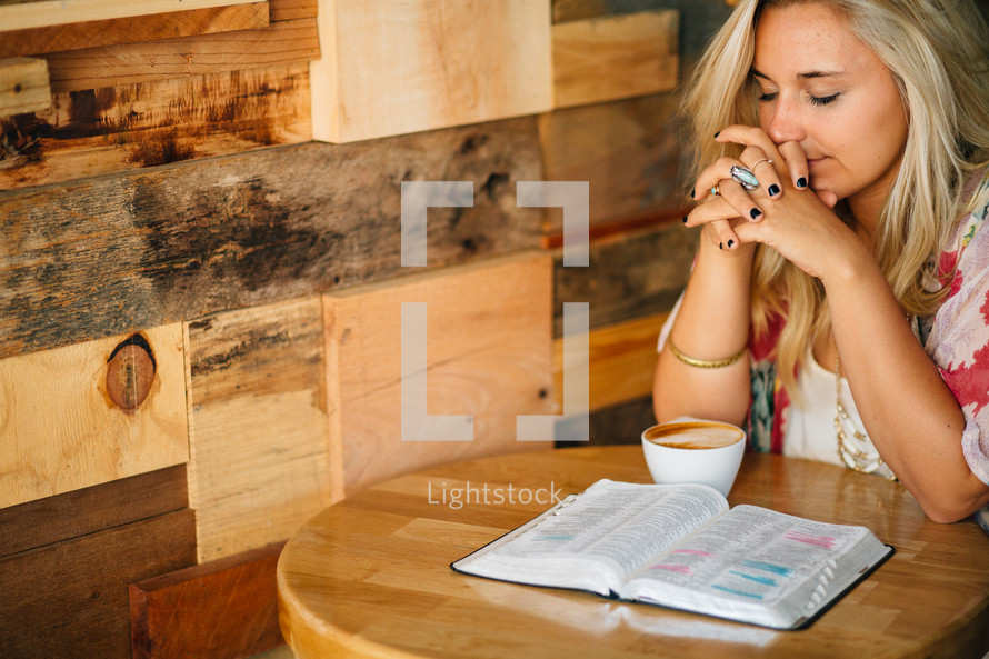 A young woman in prayer, with an open Bible and cup of coffee.
