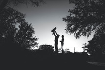 silhouette of a father holding his toddler daughter in the air