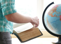 teen girl reading a Bible next to a globe