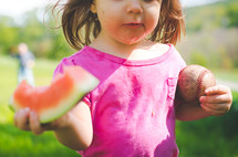 a messy child holding a watermelon and ball
